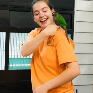 Girl with a Green Cheek Conure on her shoulder at Friendly Pets